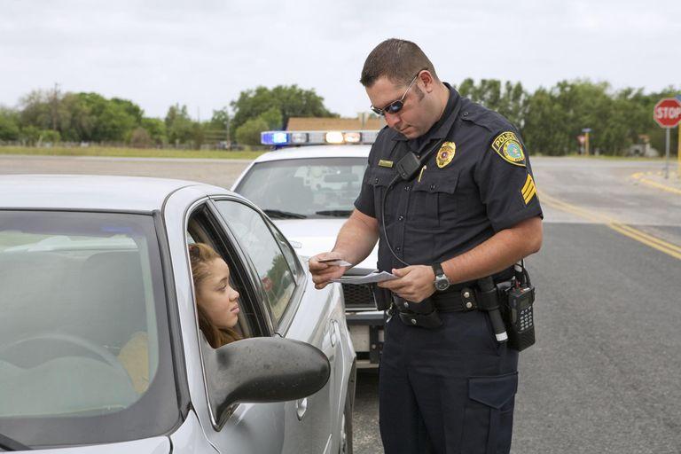 Police officer examining license of teenage girl (16-17)