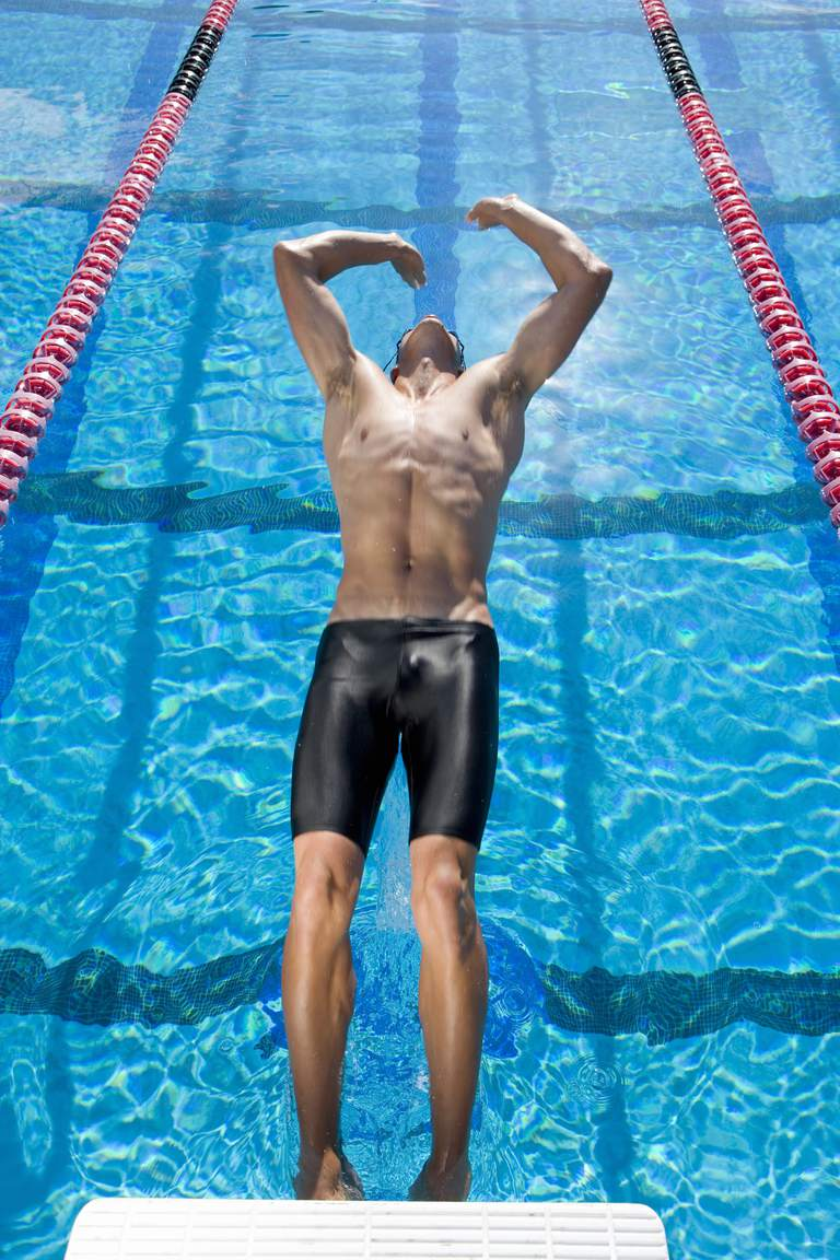Male swimmer diving into swimming pool backwards.