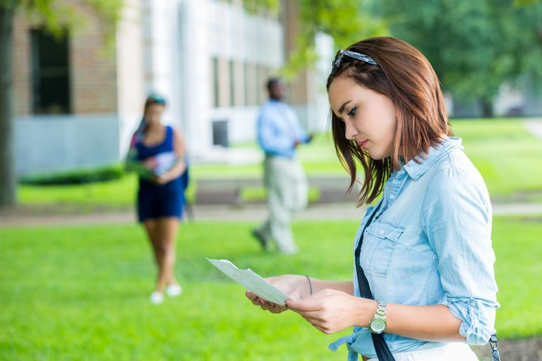 Serious college student studies class schedule on campus
