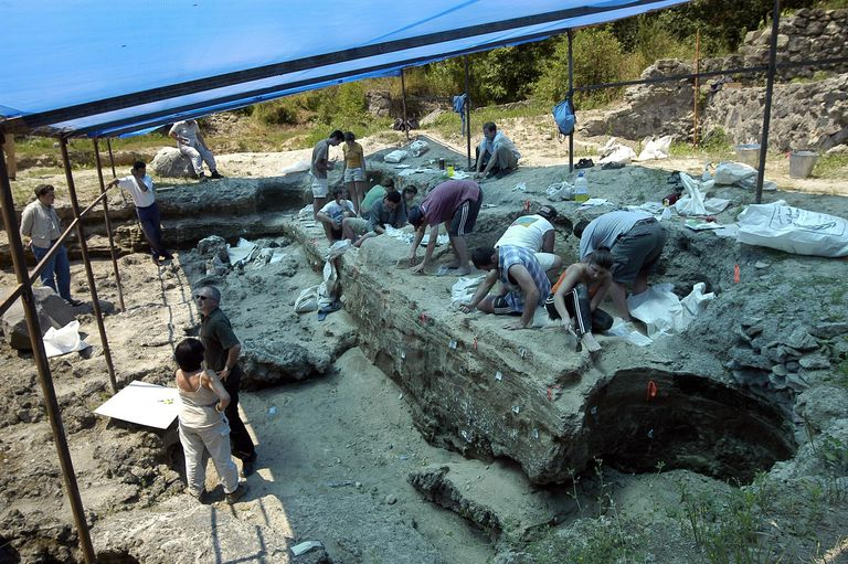 A large team of people working under a tent at an excavation site