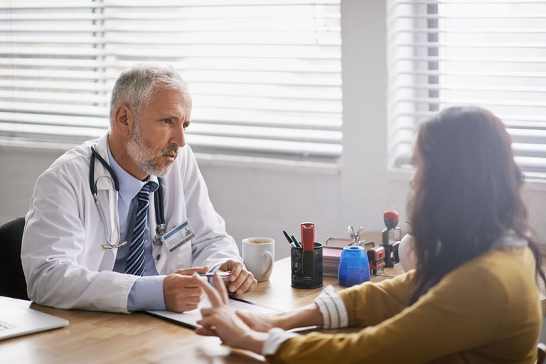 Doctor having serious conversation with woman