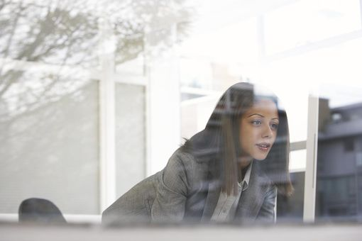 Businesswoman looking at computer, through window