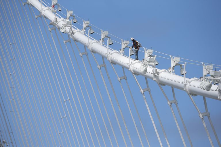 A bridge worker walks up a cable of the newly constructed San Francisco-Oakland Bay Bridge on July 12, 2013 in Oakland, California
