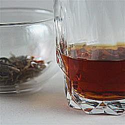 An image of Black tea Vodka and the Yunnan Golden Buds tealeaves used to infuse it.
