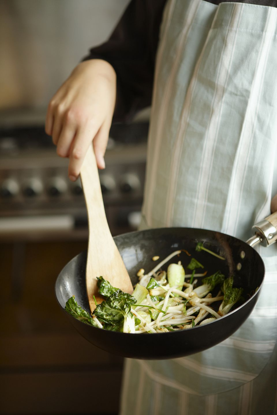Woman wearing striped apron using wooden spatula to stir fry
