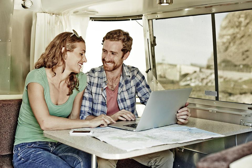 A young couple looking at a map and laptop.