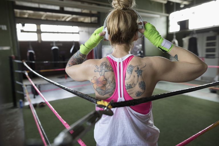 Rear view tattooed woman boxer listening to music with headphones in boxing ring at gym