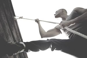 Man using rope to climb obstacle wall, low angle view