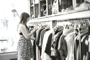Mid adult woman searching clothes rail in vintage boutique
