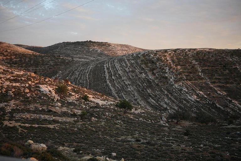 Vertical geological strata lines created millions of years ago by interior geological forces seen in the Mountains under a beautiful cloud formation at sunset. By road 443 along the Ascent of Beit Hor...