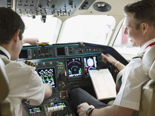Male pilot and co-pilot checking instrument panel in airplane cockpit