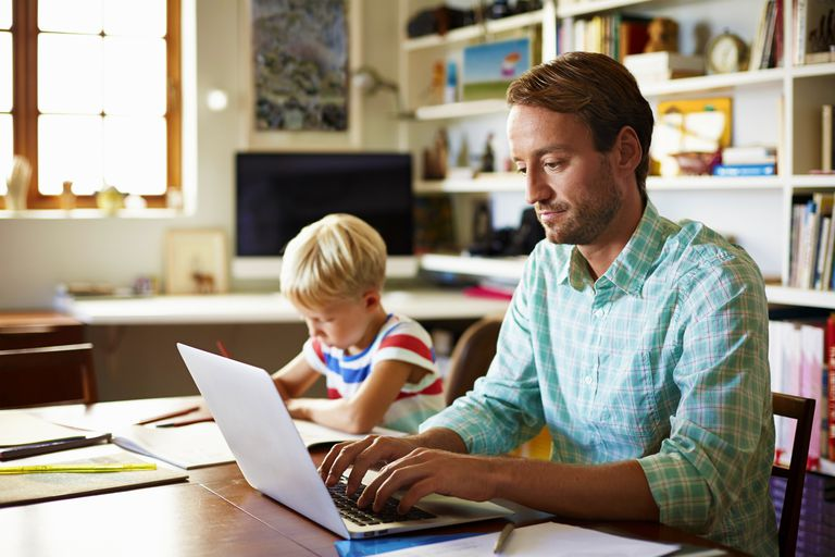 Father using laptop next to son doing schoolwork