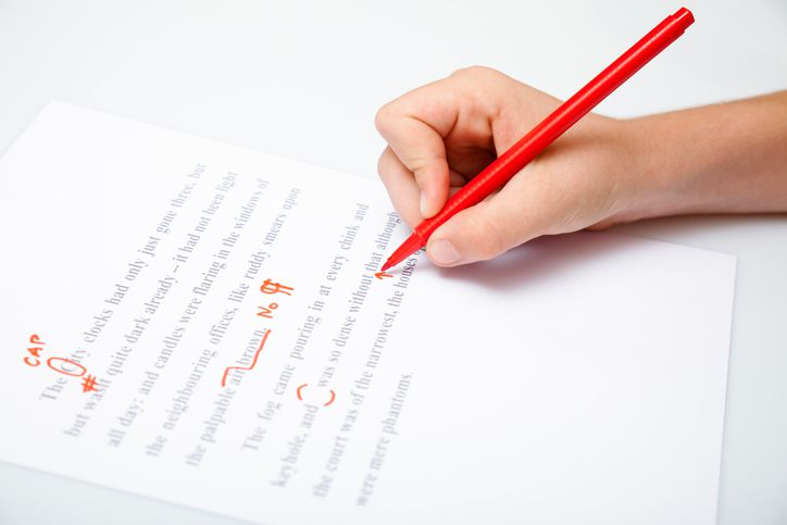 Person holding a pencil proofreading a document