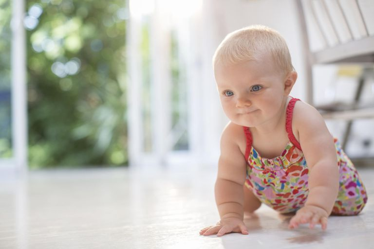 Baby girl crawling on floor