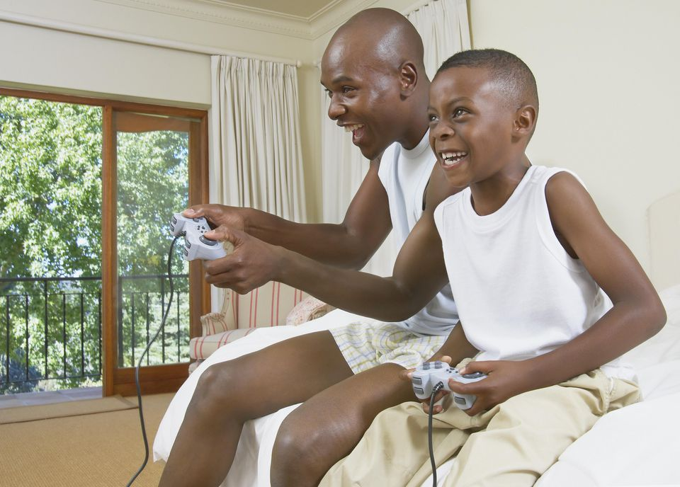 Father and son (5-7) on edge of bed playing games console, laughing