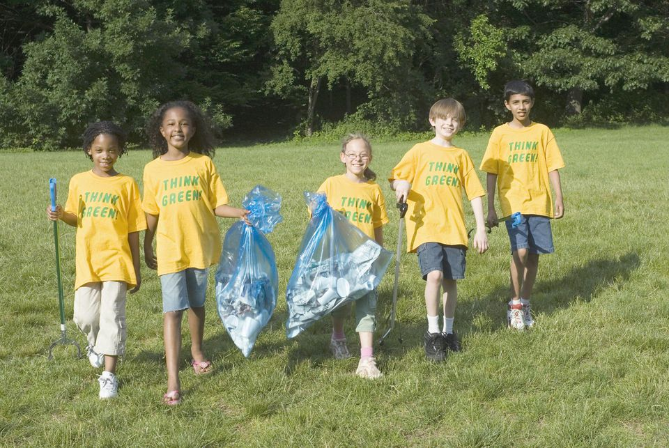 Group of children (8-10) walking with garbage bags, smiling