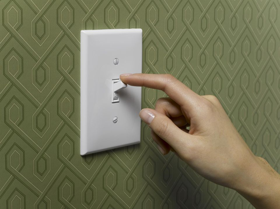 Woman turning off light switch on green wallpapered wall, close-up