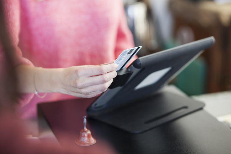 Woman sliding swiping credit card at store