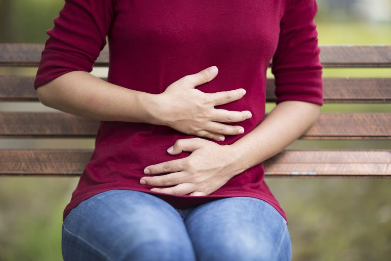 Woman Has Stomach Ache Sitting on Bench at Park