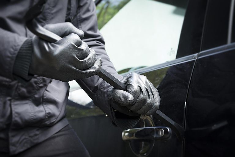 A man breaks into a car, demonstrating how deviant behavior and crime can result from structural strain.