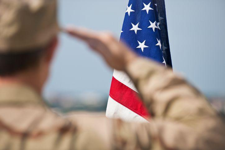 Member of the military saluting flag.