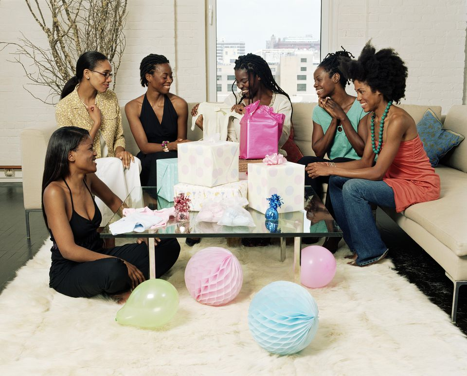 Young women having baby shower for friend