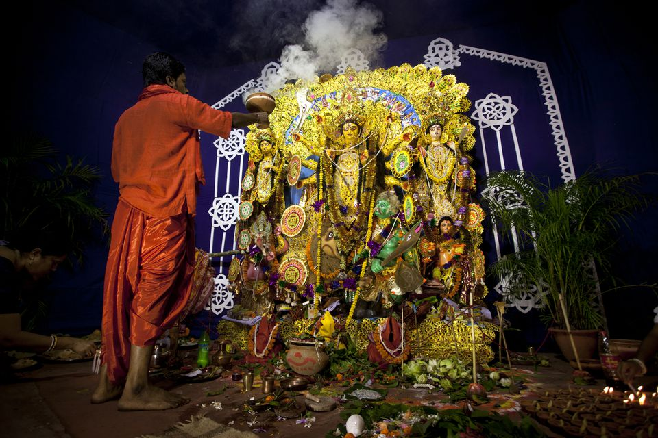 Hindu priest offers Puja to Goddess Durga