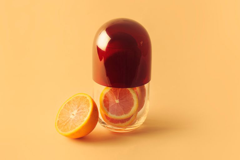 Oranges in clear capsule to represent vitamin C supplements