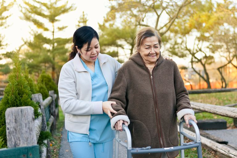 Aid helping senior woman with walker