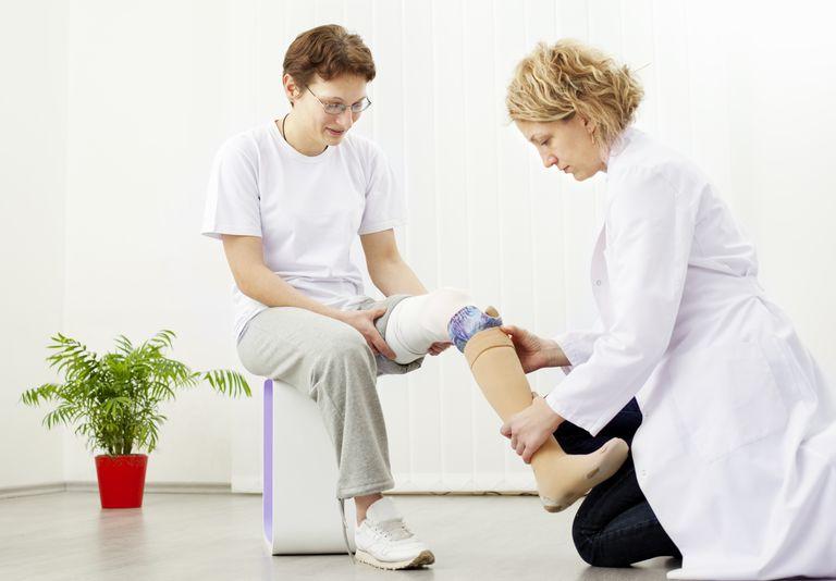 A prosthetist fits a patient's artificial limb