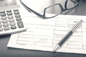 tax form sitting on desk with pen, glasses and a calculator