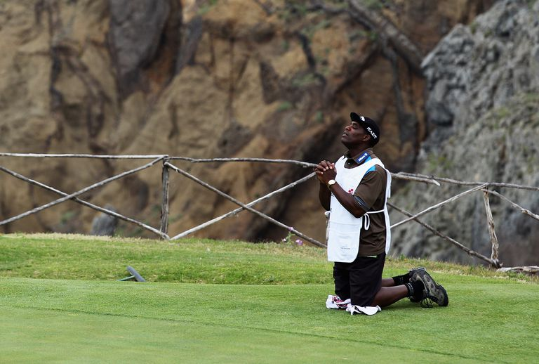 Caddie for golfer Roope Kakko prays during the Madeira Islands Open tournament.