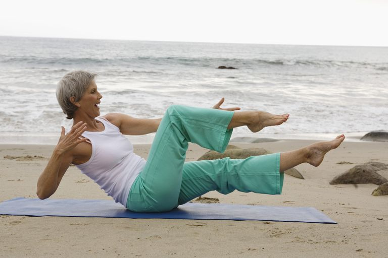Woman doing pilates on beach, Malibu, California