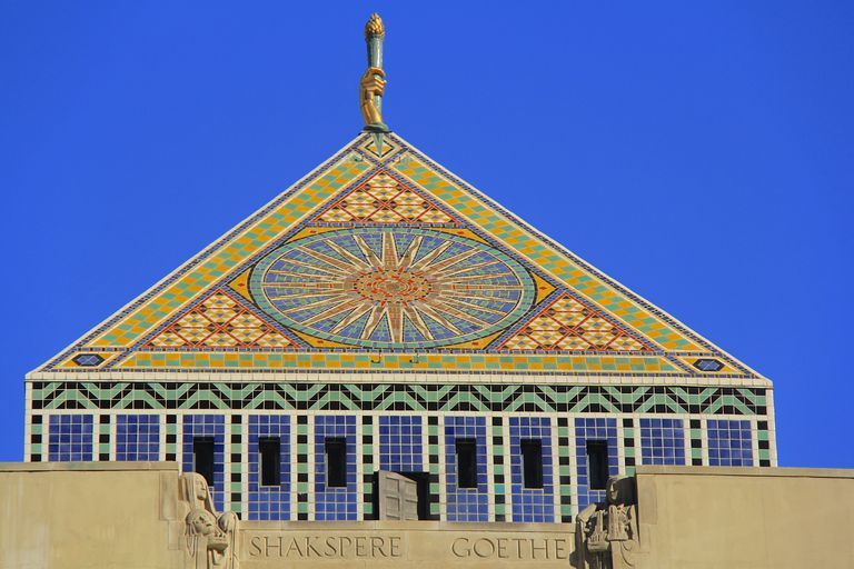 Ornate pyramid tower in colorful tiles of red, yellow, green, and blue, a sun dominates the design, the words Shakspere and Goethe are carved in stone