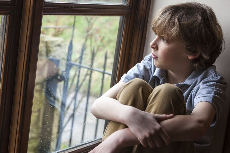 upset boy looking out a window