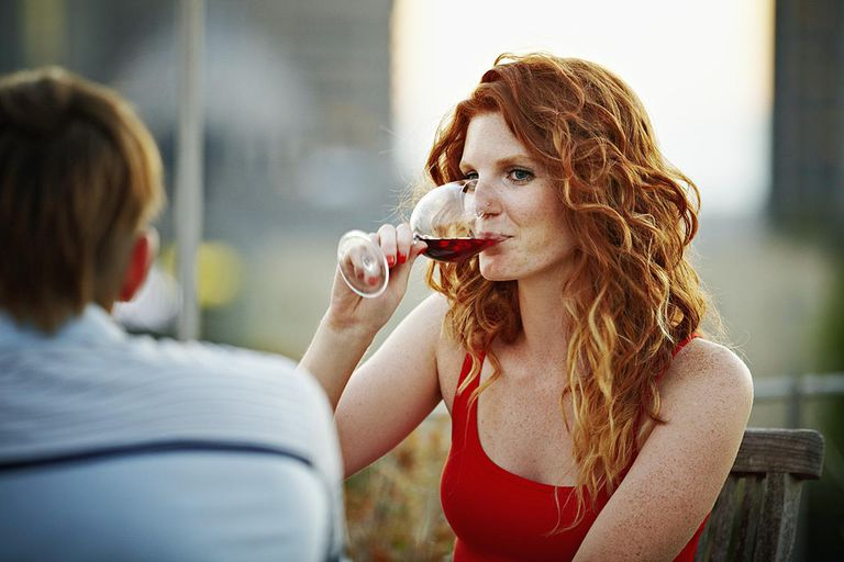Woman sitting at table on rooftop deck drinking wine at sunset cityscape in background