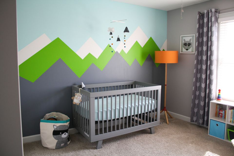 Bright and cheery nursery with mountain mural.