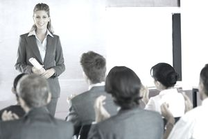 Businesswoman in Front of Clapping Crowd