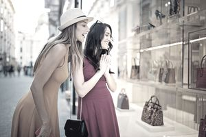 Girlfriends are looking in the bag store window