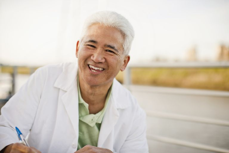 Asian doctor with white hair smiling