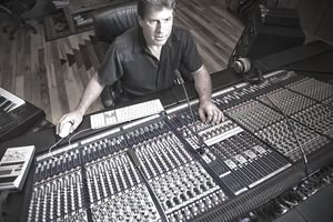 Recording Engineer at Mixing Console in a Studio