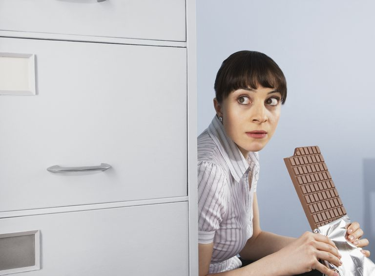 Woman hiding and eating a chocolate bar.