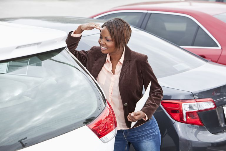 Woman in car lot looking at cars