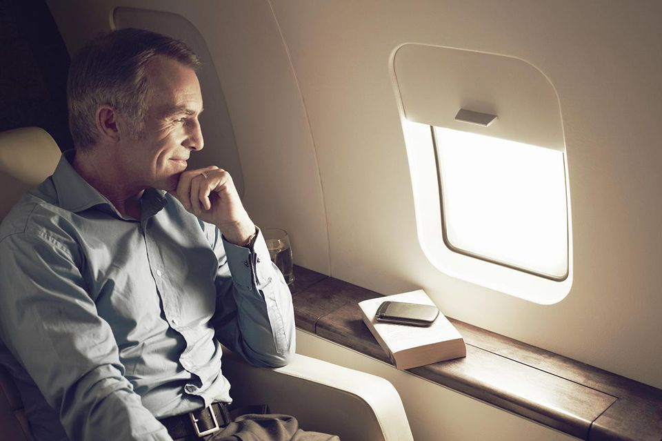Businessman gazing out of window aboard flight
