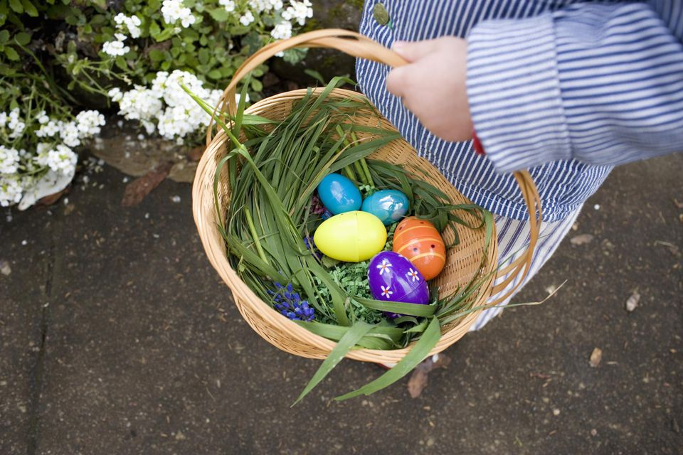 Baby boy (12-15 months) carrying basket of Easter eggs, low section