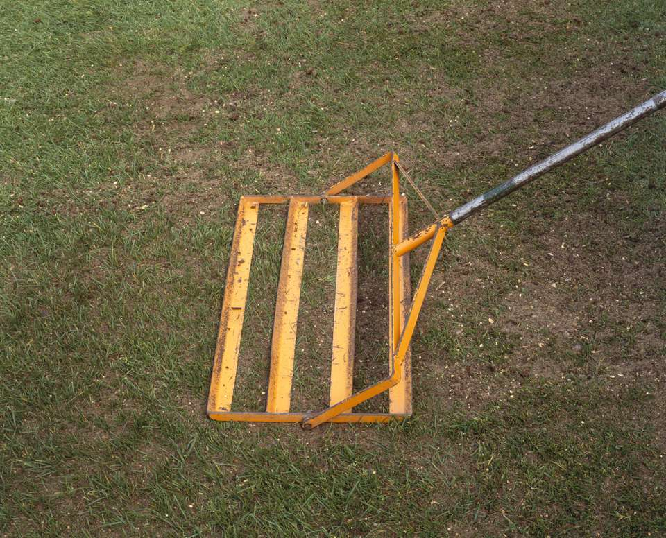 Using a lute to work in top dressing on a lawn