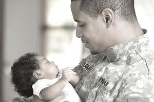 Returning African soldier holding newborn baby
