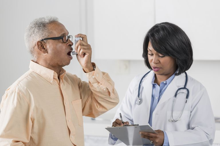 African American doctor with man using asthma inhaler