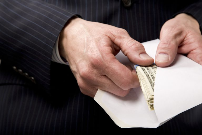 A man pulling money from an envelope.