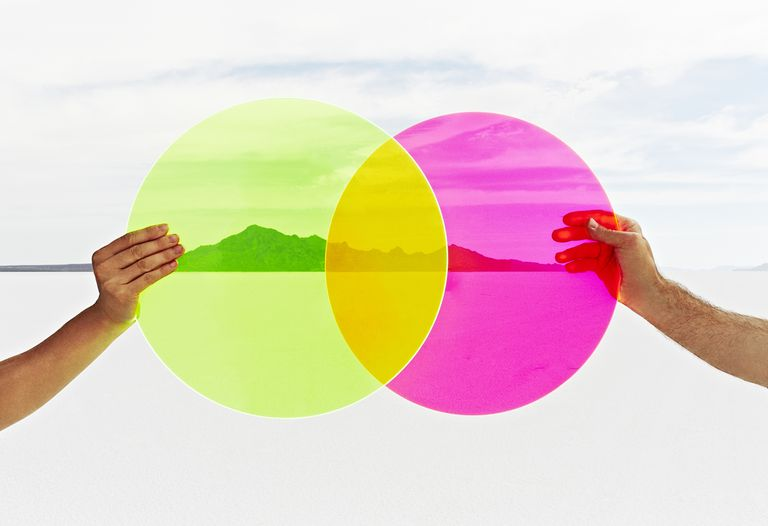 Two hands holding colored circles in landscape